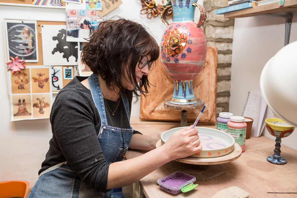 Leyla Folwell painting a commissioned plate