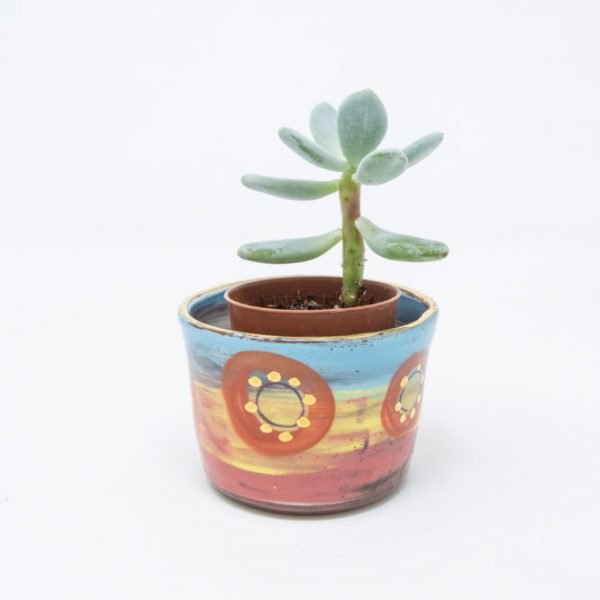 Yellow, pink and blue ceramic plant pot with orange circles and dots of gold luster holding a small succulent plant