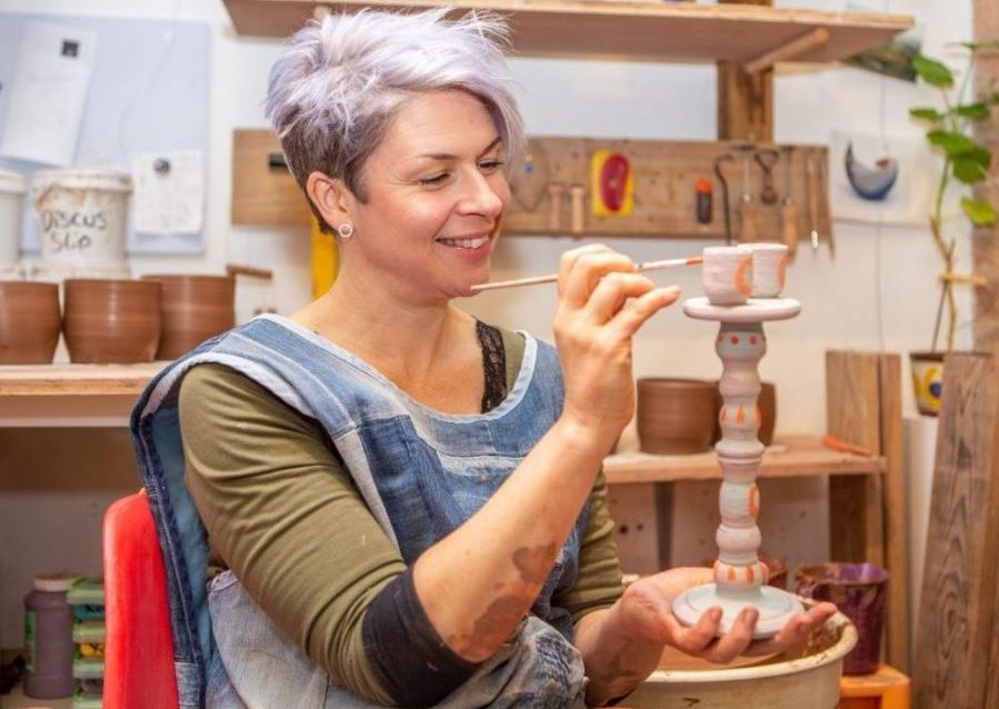 Leyla adding glaze to a ceramic candlestick