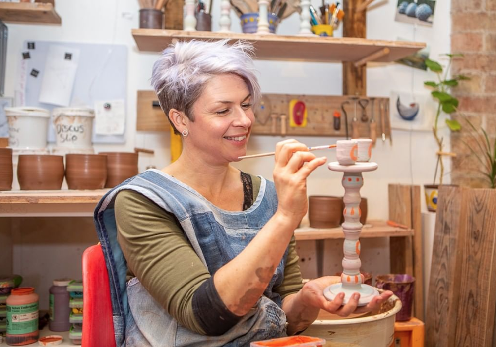 Leyla Folwell painting a ceramic candle stick